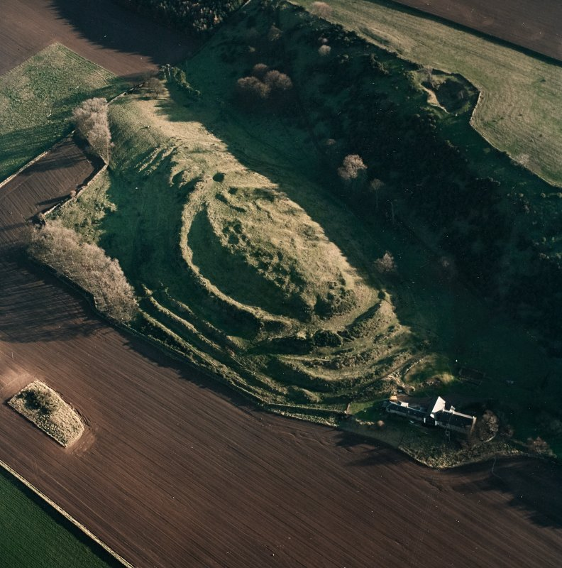 Oblique aerial view centred on the remains of the fort with farmsteading adjacent, taken from the WNW.