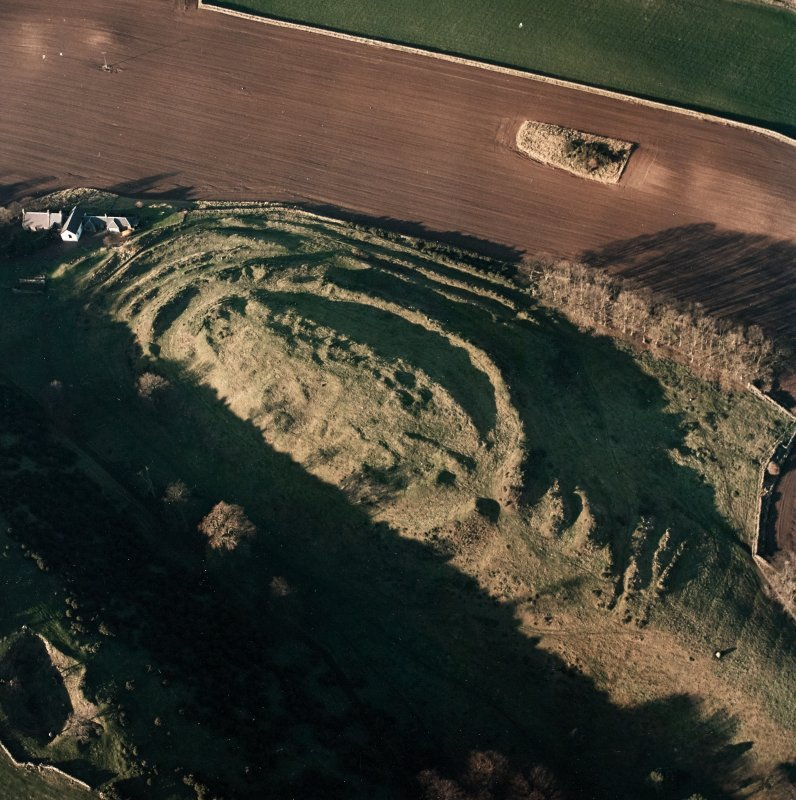 Oblique aerial view centred on the remains of the fort with farmsteading adjacent, taken from the SE.