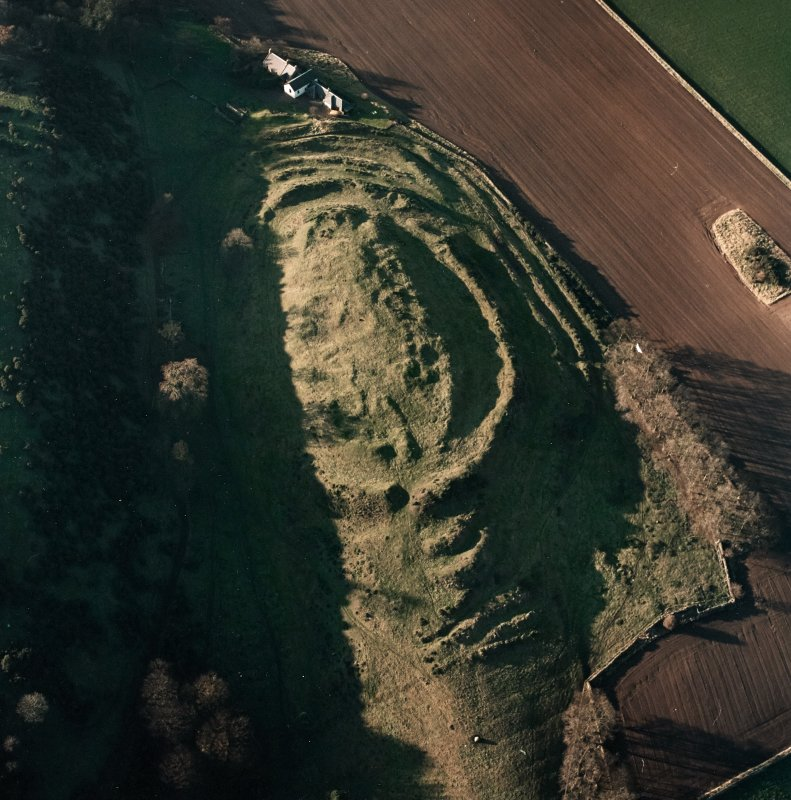 Oblique aerial view centred on the remains of the fort with farmsteading adjacent, taken from the ESE.