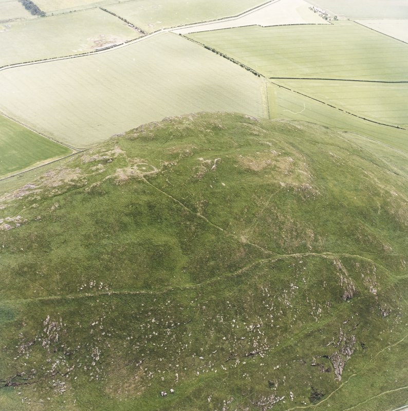 Oblique aerial view centred on the remains of the fort and cairn, taken from the N.