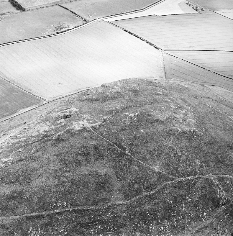 Oblique aerial view centred on the remains of the fort and cairn, taken from the S.