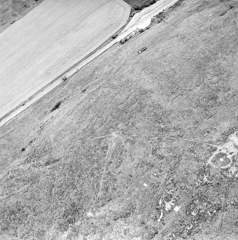 Oblique aerial view centred on the remains of the fort and cairn, taken from the SW.