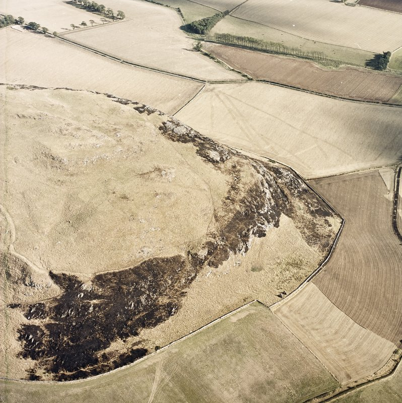 Oblique aerial view centred on the remains of the fort showing recent fire damage, taken from the NW.