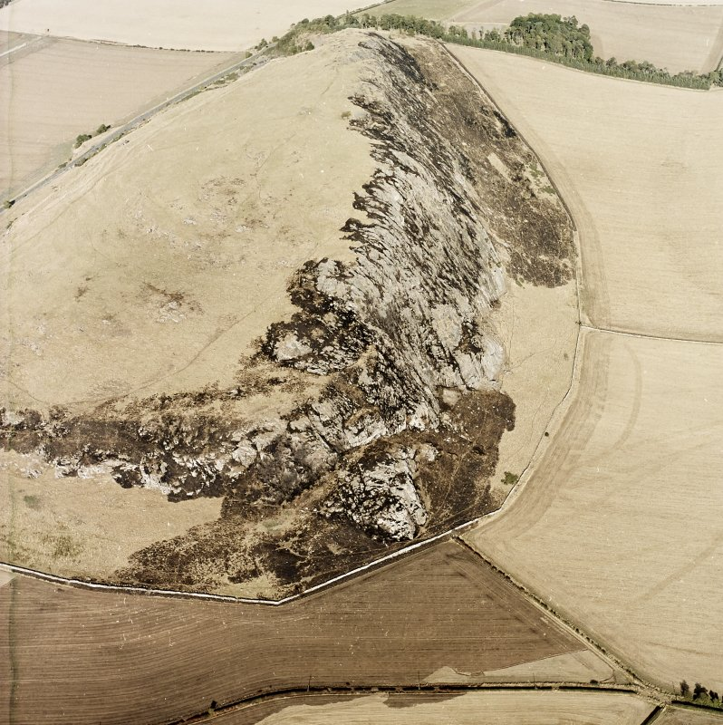 Oblique aerial view centred on the remains of the fort showing recent fire damage, taken from the SW.