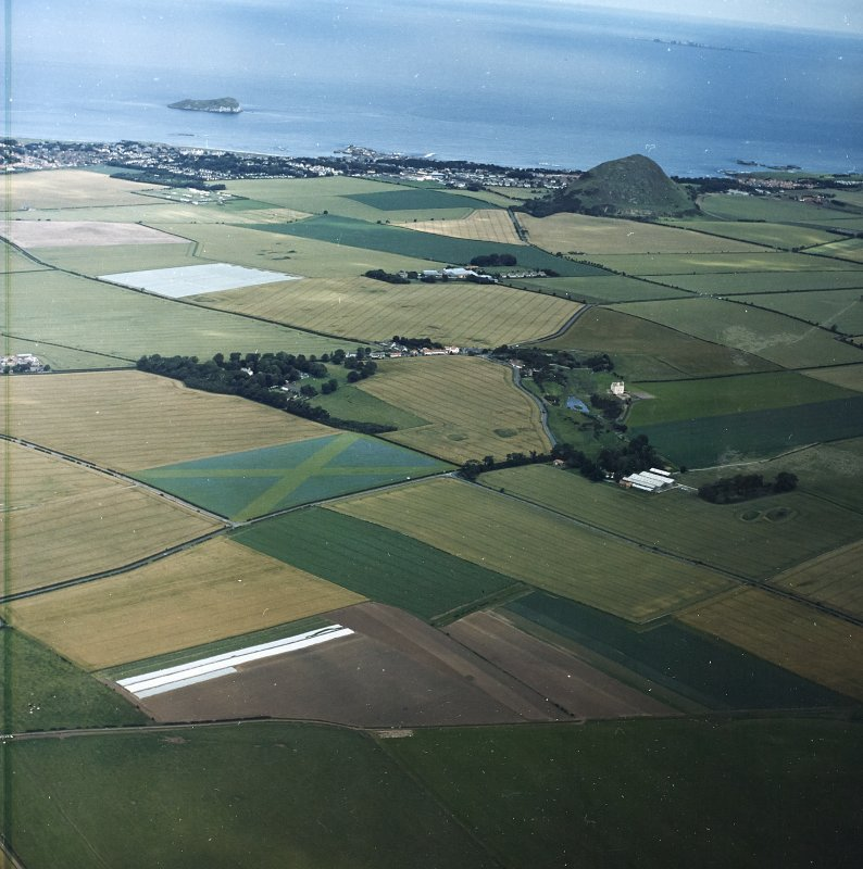 General oblique aerial view looking across Fenton tower-house, towards the remains of the fort and North Berwick beyond, taken from the SW.