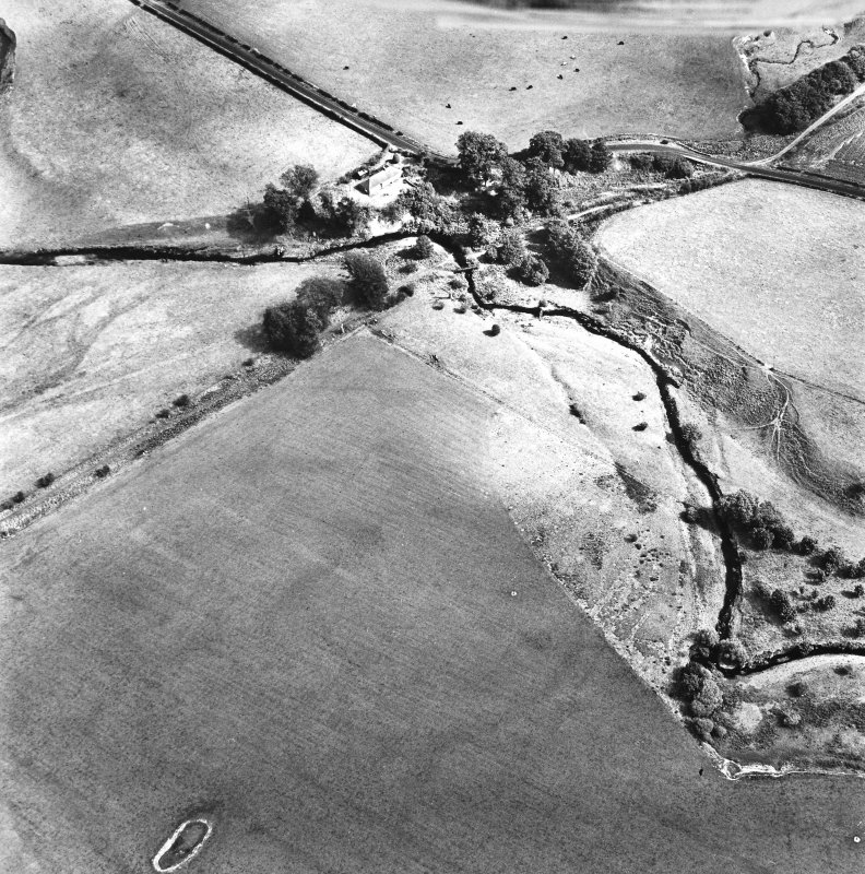 Cappuck, oblique aerial view, taken from the ESE, centred on the cropmark of an enclosure. The site of a Roman Fort is shown in the top right-hand side of the photograph.