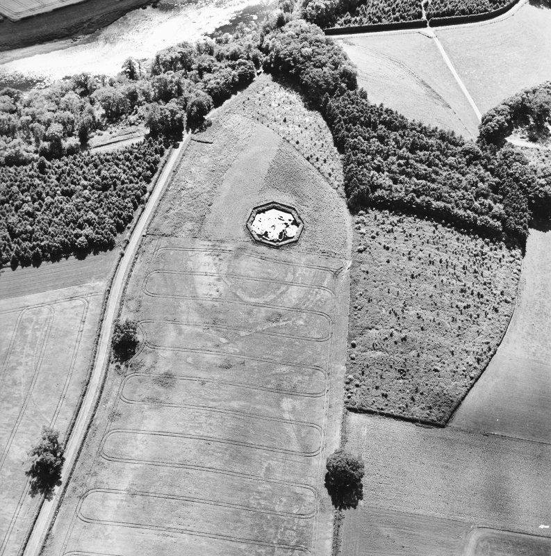 Brox Law, oblique aerial view, taken from the NE, centred on the cropmark of a fort which is partially overlain by a pond.