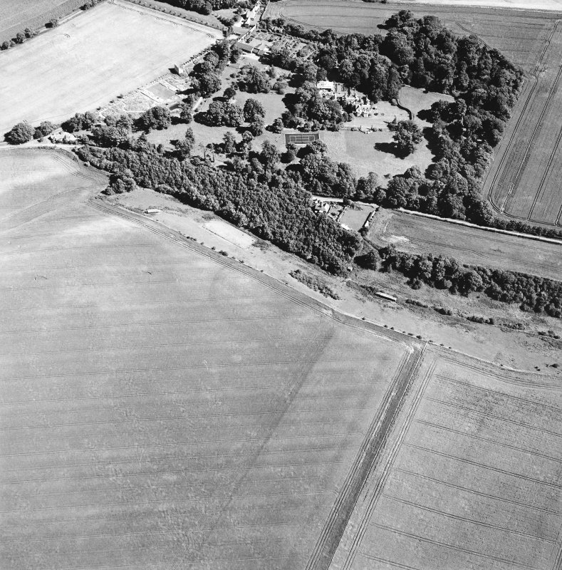 Oblique aerial view centred on the cropmarks of the settlement with the country house adjacent, taken from the WNW.