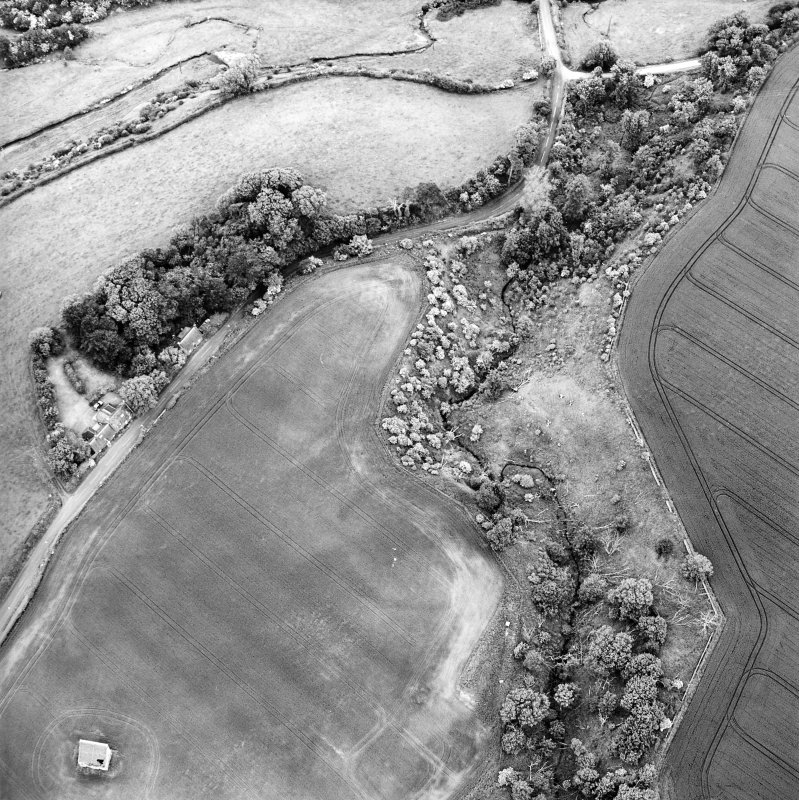 Oblique aerial view centred on the cropmarks of the enclosure with dovecot adjacent, taken from the S.