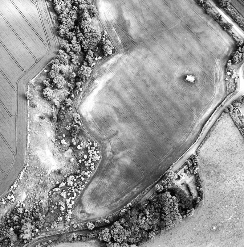 Oblique aerial view centred on the cropmarks of the enclosure with dovecot adjacent, taken from the NNW.