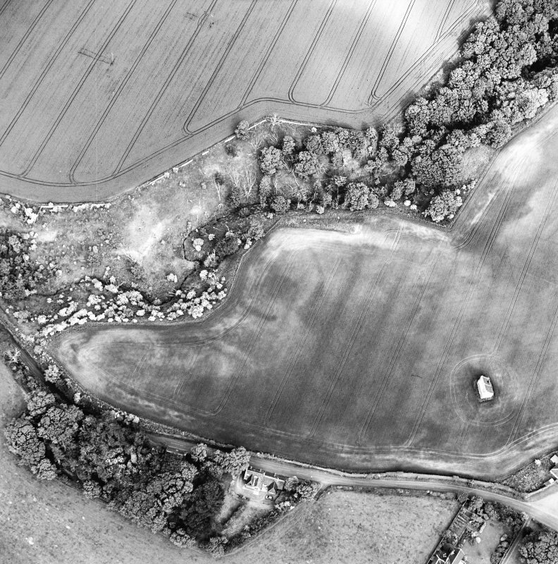 Oblique aerial view centred on the cropmarks of the enclosure with dovecot adjacent, taken from the WNW.
