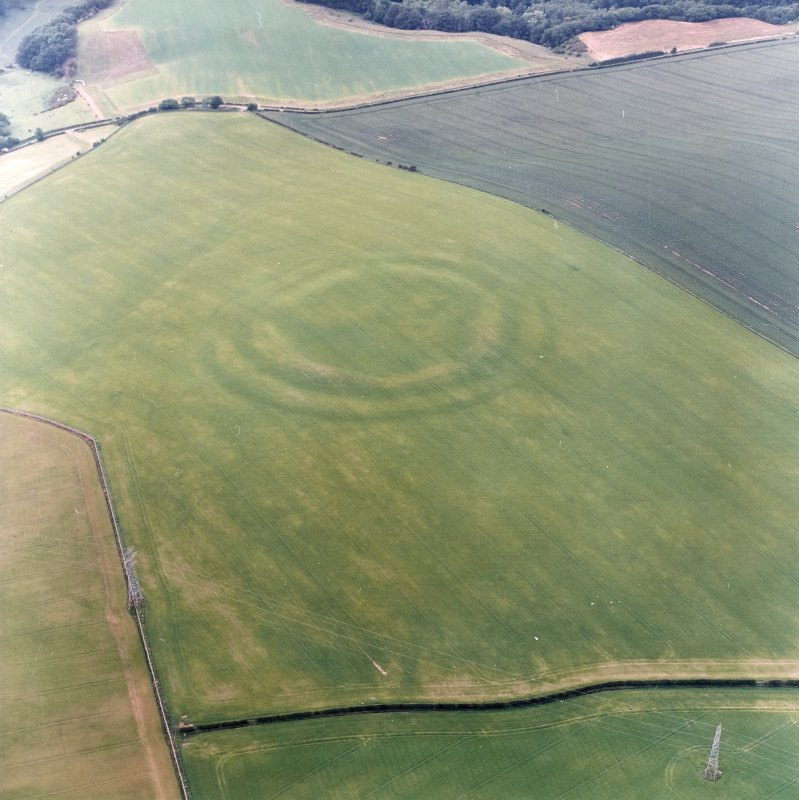 Oblique aerial view centred on the cropmarks of the fort with field boundaries and  cropmarks adjacent, taken from the SSE.