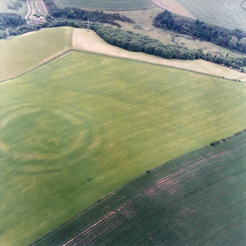 Oblique aerial view centred on the cropmarks of the field boundaries and cropmarks with fort adjacent, taken from the ENE.