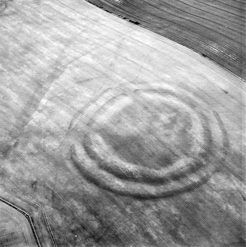 Oblique aerial view centred on the cropmarks of the fort with field boundaries and  cropmarks adjacent, taken from the S.