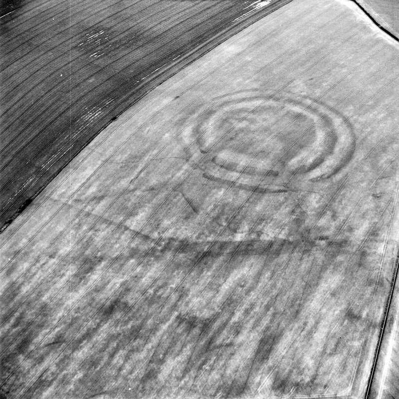 Oblique aerial view centred on the cropmarks of the fort with field boundaries and  cropmarks adjacent, taken from the W.