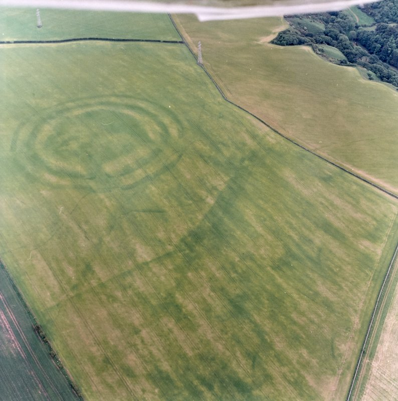Oblique aerial view centred on the cropmarks of the field boundaries and cropmarks with fort adjacent, taken from the NNW.