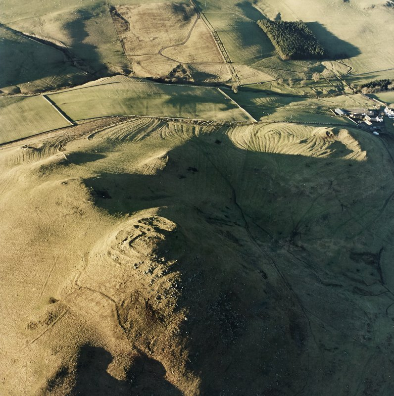 Oblique aerial view centred on the remains of the fort with rig, enclosures and cairn adjacent, taken from the SE.