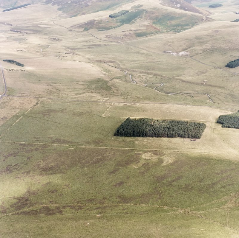 Pennymuir, oblique aerial view, taken from the WNW, centred on three Roman Temporary Camps, a linear earthwork and an area of rig. The course of 'Dere Street' is visible in the centre of the photograph.