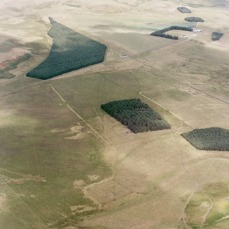 Pennymuir, oblique aerial view, taken from the SW, centred on Roman Temporary Camps, a linear earthwork and an area of rig. The course of 'Dere Street' is visible in the top right half of the photograph.