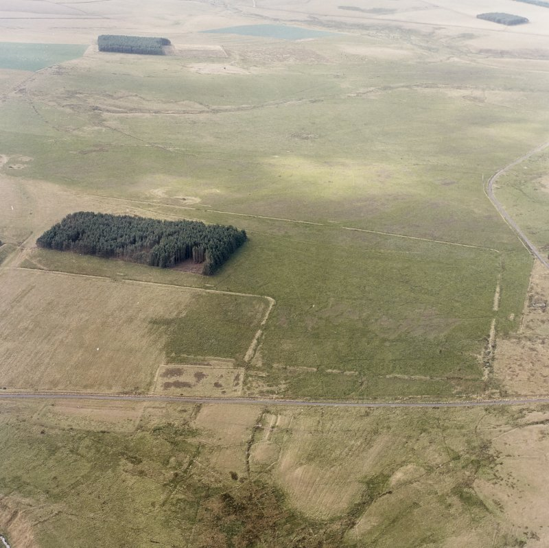Pennymuir, oblique aerial view, taken from the ENE, centred on three Roman Temporary Camps, a linear earthwork and an area of rig. The course of 'Dere Street' is visible in the bottom half of the photograph.