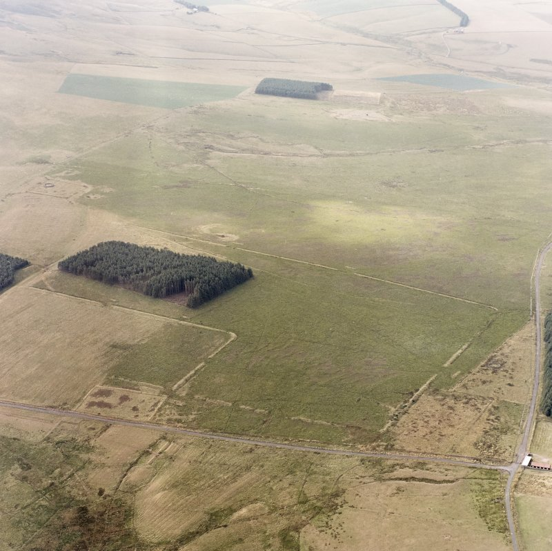 Pennymuir, oblique aerial view, taken from the NE, centred on three Roman Temporary Camps, a linear earthwork and an area of rig. The course of 'Dere Street' is visible in the bottom half of the photograph.