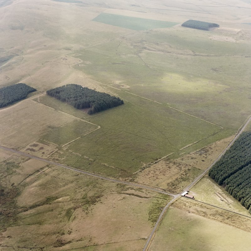 Pennymuir, oblique aerial view, taken from the NE, centred on Roman Temporary Camps, a linear earthwork and an area of rig. The course of 'Dere Street' is visible in the bottom half of the photograph.