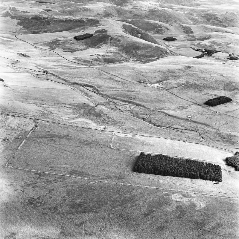 Pennymuir, oblique aerial view, taken from the WSW, centred on three Roman Temporary Camps, a linear earthwork and an area of rig. The course of 'Dere Street' is shown in the centre of the photograph.