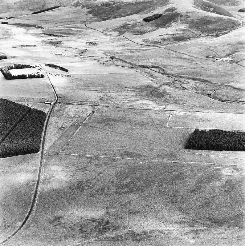 Pennymuir, oblique aerial view, taken from the WSW, centred Roman Temporary Camps, a linear earthwork and an area of rig. The course of 'Dere Street' is shown in the centre of the photograph.