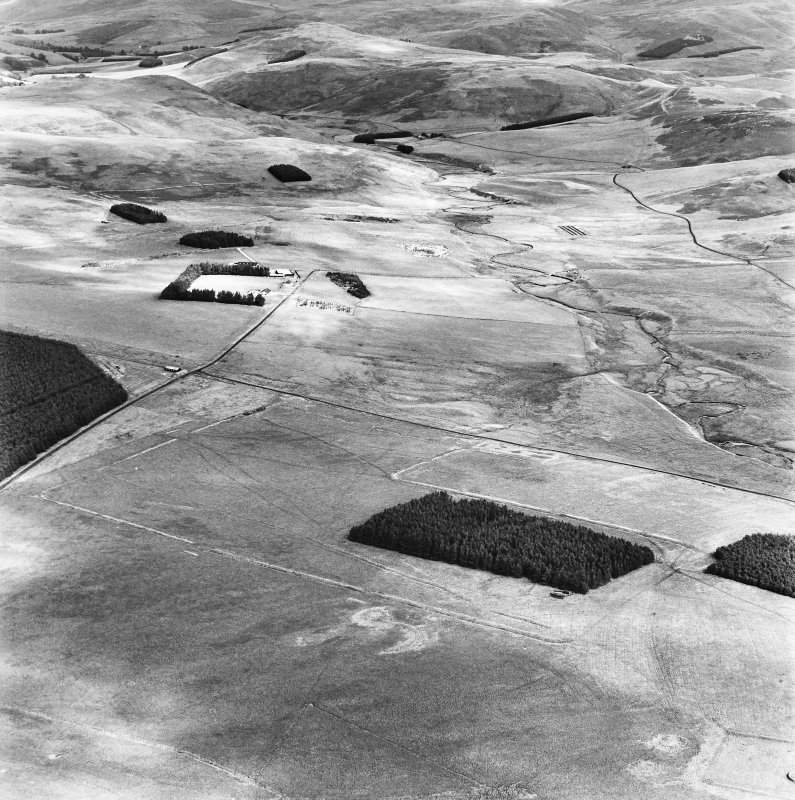 Pennymuir, oblique aerial view, taken from the SW, centred on Roman Temporary Camps, a linear earthwork and an area of rig. The course of 'Dere Street' is shown in the centre of the photograph.
