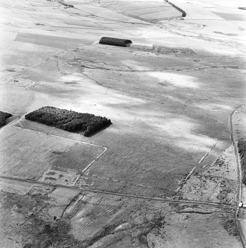 Pennymuir, oblique aerial view, taken from the WNW, centred on three Roman Temporary Camps, a linear earthwork and an area of rig. The course of 'Dere Street' is visible in the bottom half of the photograph.
