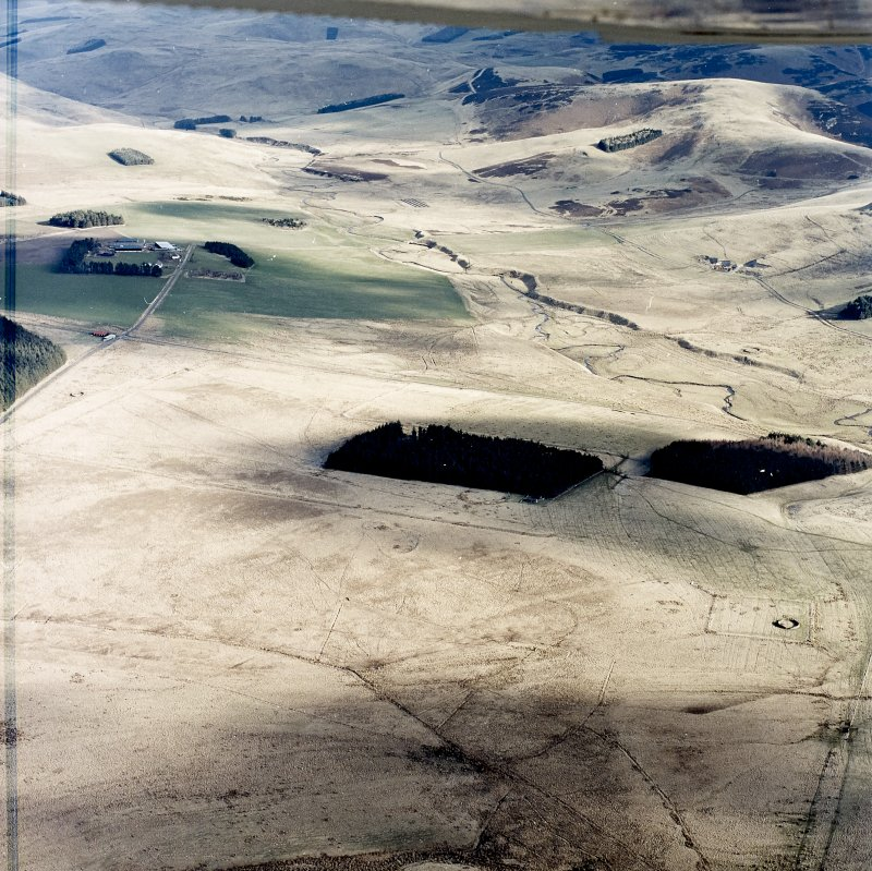Oblique aerial view centred on the remains of Roman temporary camps, earthwork, sheepfolds, enclosure and rig, taken from the SW.