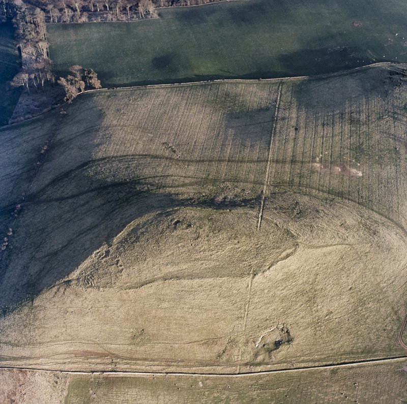 Oblique aerial view centred on the remains of the fort and settlement, taken from the NW.