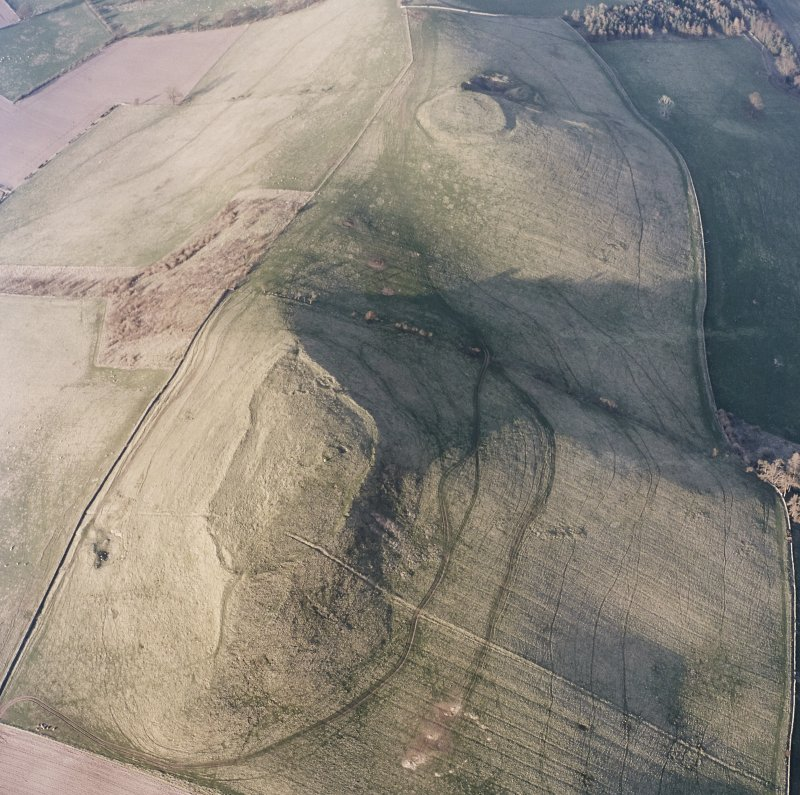 Oblique aerial view centred on the remains of the fort and settlement with fort adjacent, taken from the SW.