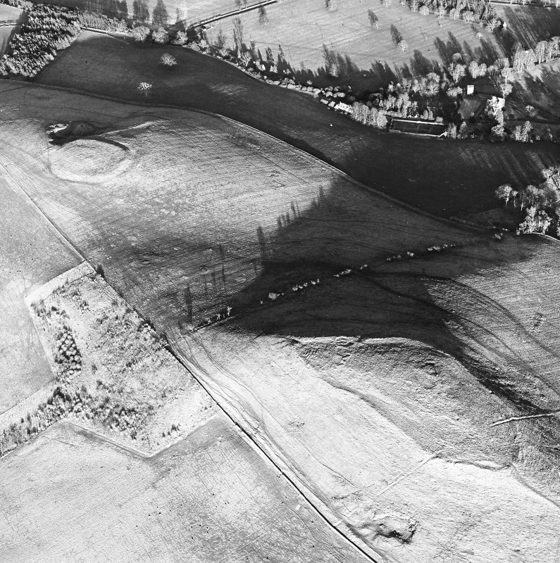 Oblique aerial view centred on the remains of the fort and settlement with fort adjacent, taken from the WSW.