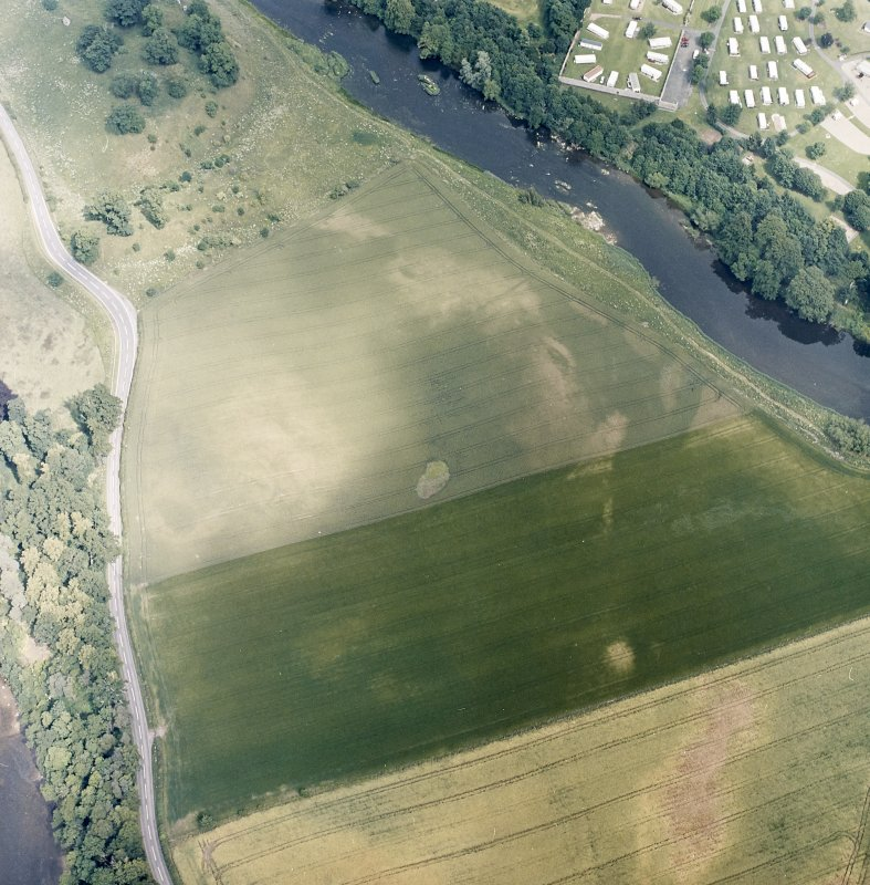 Oblique aerial view centred on the linear cropmarks and cropmarks with the remains of the castle and the cauld adjacent, taken from the SW.