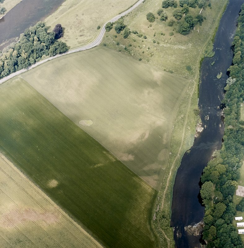 Oblique aerial view centred on the linear cropmarks and cropmarks with the remains of the castle and the cauld adjacent, taken from the S.