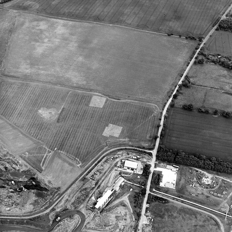 Oblique aerial view centred on the trial excavations with the cement works and quarry adjacent, taken from the W.