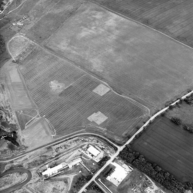 Oblique aerial view centred on the trial excavations with the cement works and quarry adjacent, taken from the WSW.