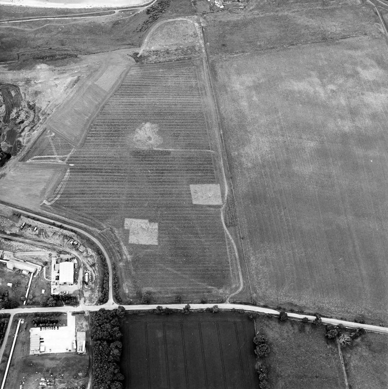 Oblique aerial view centred on the trial excavations with the cement works and quarry adjacent, taken from the SSW.