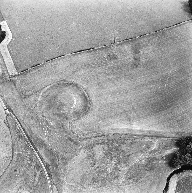 Oblique aerial view centred on the remains of the motte-and-bailey castle, taken from the W.