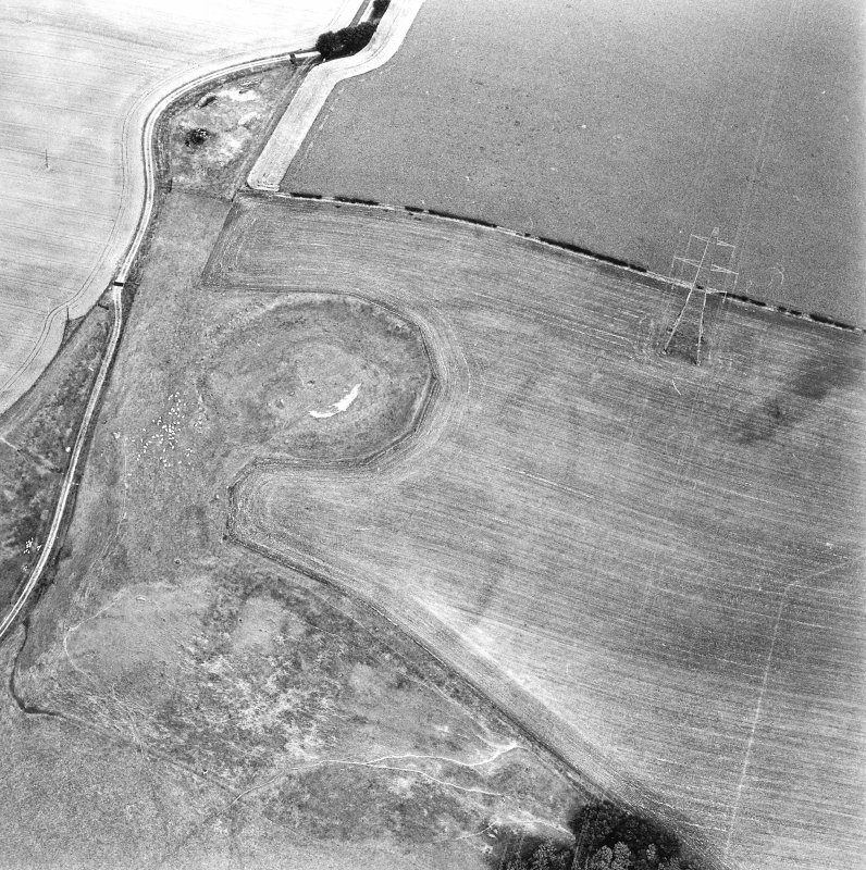Oblique aerial view centred on the remains of the motte-and-bailey castle, taken from the SW.