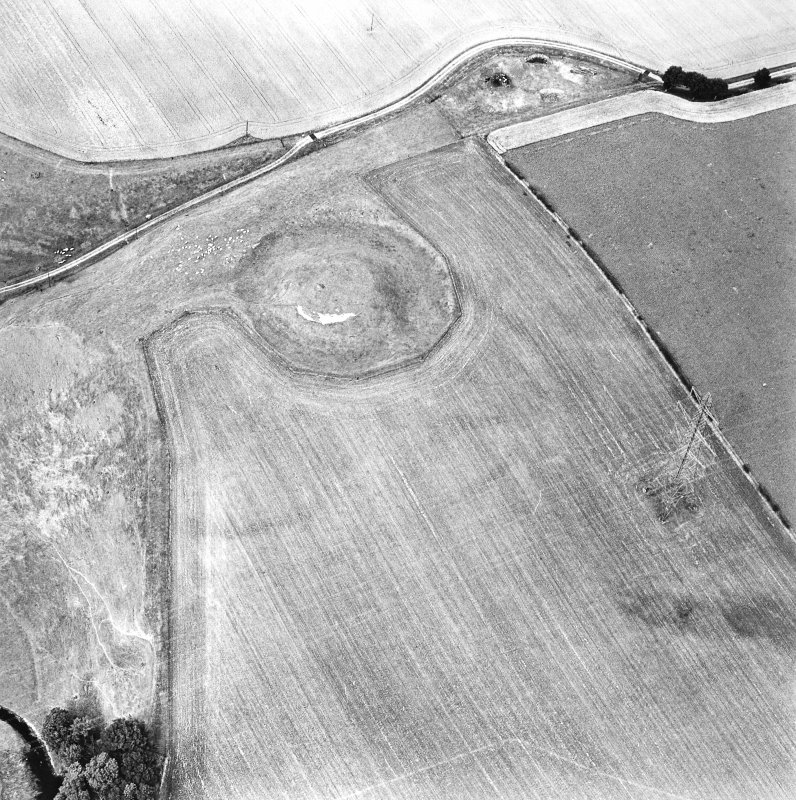Oblique aerial view centred on the remains of the motte-and-bailey castle, taken from the S.