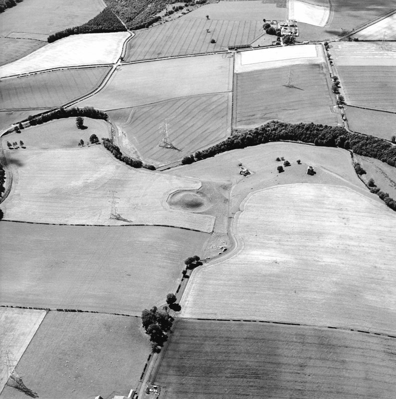 Oblique aerial view centred on the remains of the motte-and-bailey castle with the remains of the country house adjacent, taken from the NE.