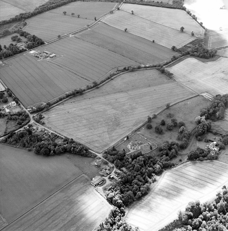 Oblique aerial view centred on the cropmarks of the possible enclosures and linear cropmarks with the church, burial ground, manse, country house, lodge, school, farmhouses, farmsteadings and cottages adjacent, taken from the NE.