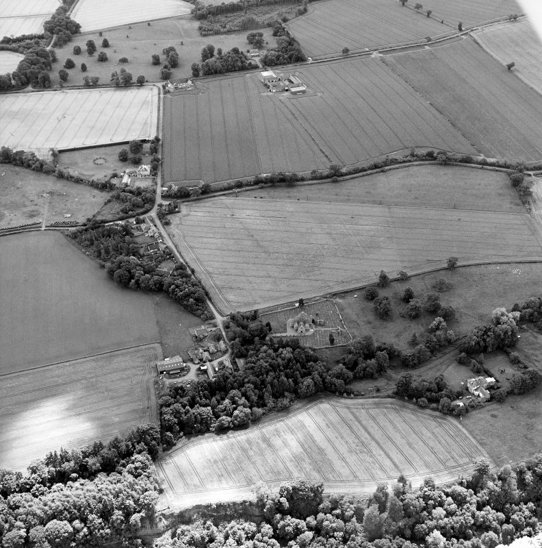 Oblique aerial view centred on the cropmarks of the possible enclosures and linear cropmarks with the church, burial ground, manse, country house, lodge, school, farmhouses, farmsteadings and cottages adjacent, taken from the NNE.