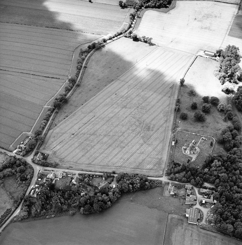 Oblique aerial view centred on the possible enclosures and linear cropmarks with the church, burial ground, lodge, school, farmhouses, farmsteadings and cottages adjacent, taken from the ENE.