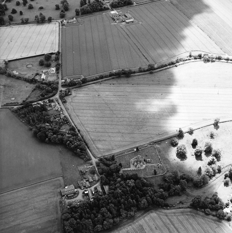 Oblique aerial view centred on the possible enclosures and linear cropmarks with the church, burial ground, manse, lodge, school, farmhouses, farmsteadings and cottages adjacent, taken from the NNE.