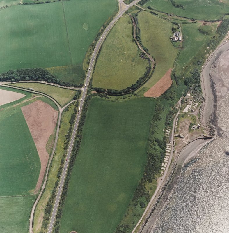 Innermessan, oblique aerial view, taken from the NNW, centred on the cropmarks of a possible enclosure, and showing the remains of Cairnryan Military Railway and associated camp and workshops in the right half of the photograph, and Innermessan Motte in the top right-hand corner.