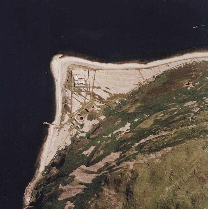 Oblique aerial view centred on the lighthouse, cottages and foghorn with the remains of the castle adjacent, taken from the NW.