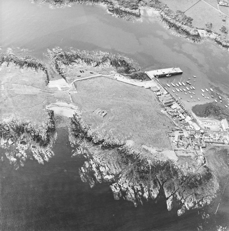 Oblique aerial view centred on the remains of the chapel with the harbour and remains of rig adjacent, taken from the NE.